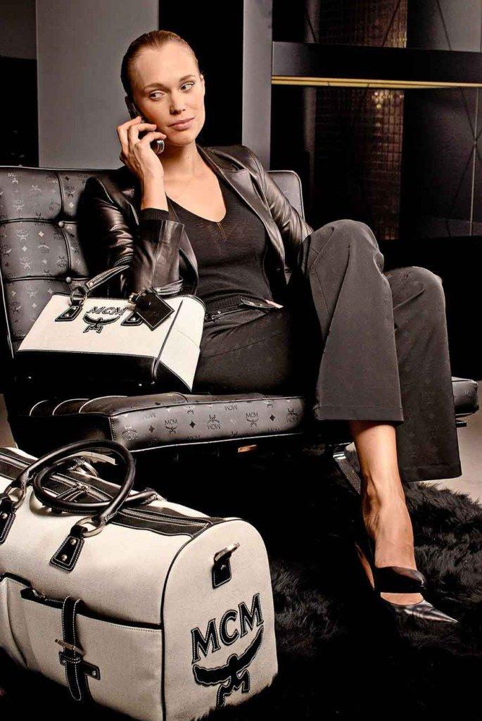 junge Dame sitzt auf einem Barcelona-Stuhl mit Taschen der Marke MCM