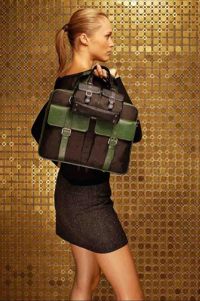 Weibliches Model steht seitlich zum Betrachter vor einer goldenen MCM-Logowand und trägt zwei Damentaschen