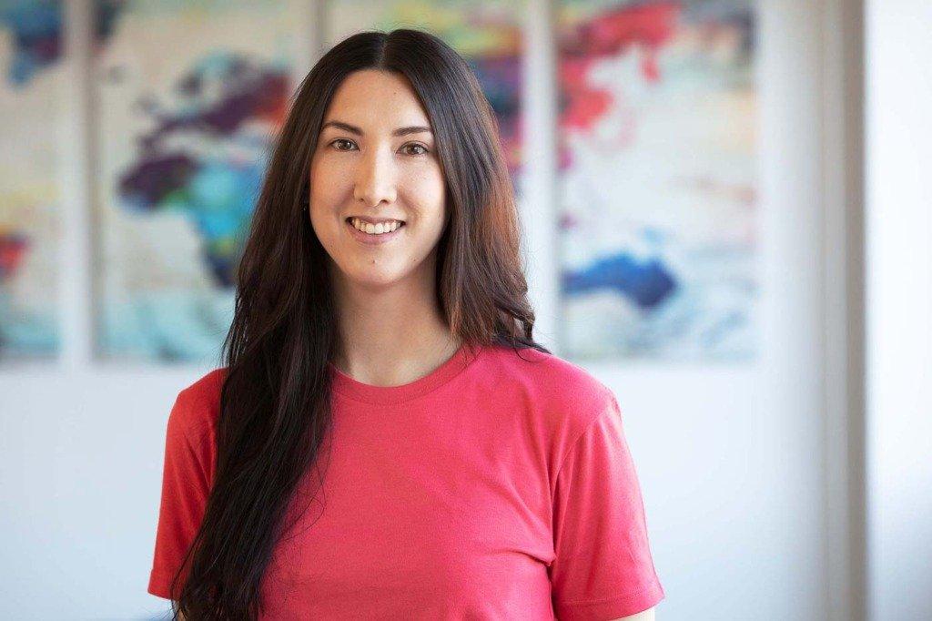 Mitarbeiterfoto von einer brünetten Frau mit rotem T-Shirt im Büro des Berliner Start-Ups Smoobu
