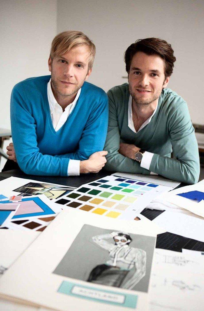 Das Modedesigner-Duo Achtland lehnt sich über Farbpaletten und Skizzen in ihrem Atelier in Berlin Kreuzberg