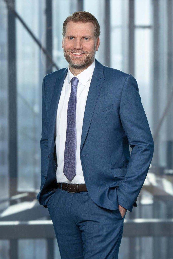 Alexander Schaumann, Partner der Baurechtskanzlei Pietschmann Legal Berlin, steht im blauen Anzug in den Räumen der Kanzlei
