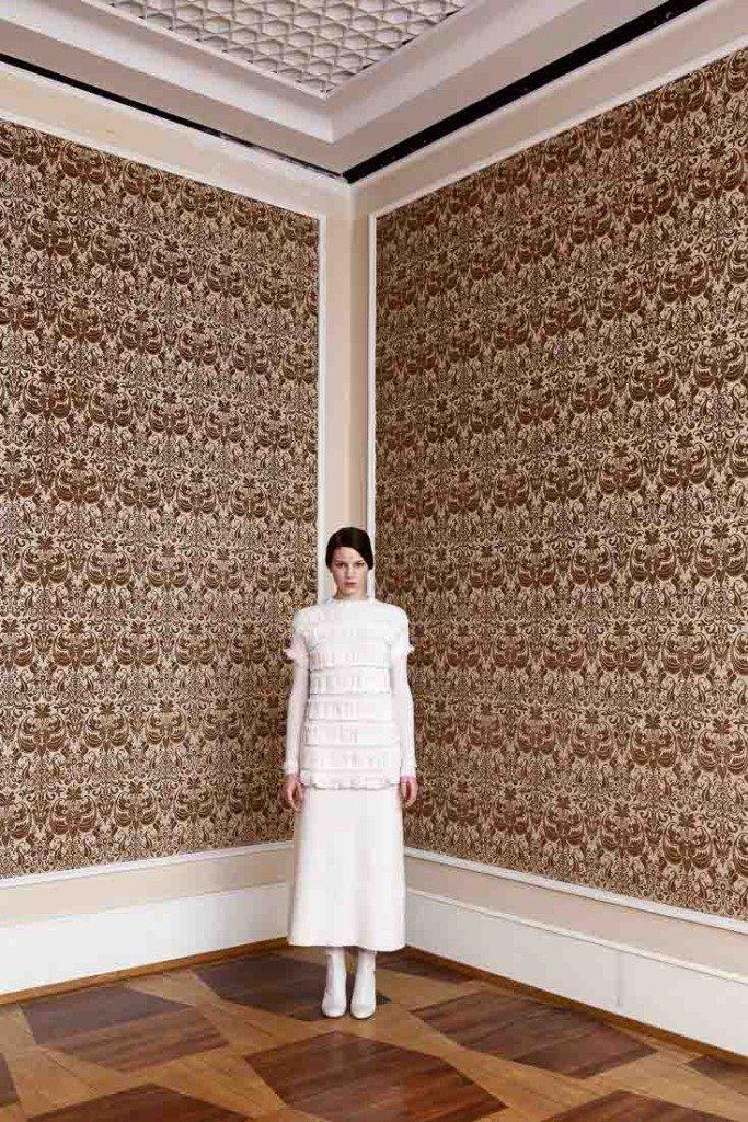 Junge Frau steht im Kronprinzessinnenpalais Berlin mit einem Outfit von Allude vor einer historischen Tapetenwand. Für Women's Wear Daily