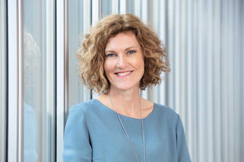 Bayer-Managerin Anna Braeken steht im hellblauen Kleid vor einer Metall-Glas-Wand im Berliner Firmensitz