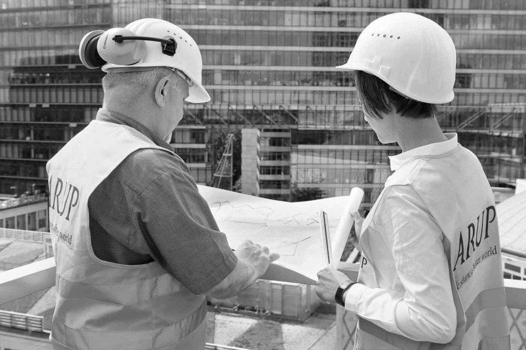 Zwei Bauingenieure der Firma Arup stehen mit Helmen auf einer Baustelle und blicken auf einen Bauplan