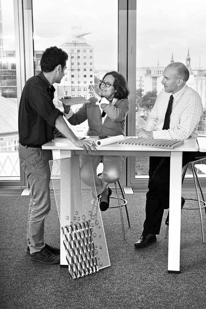 Drei Ingenieure diskutieren Bau-Materialien für die Innenakustik. Die Mitarbeiter von Arup meeten in dessen Berliner Büroräumen
