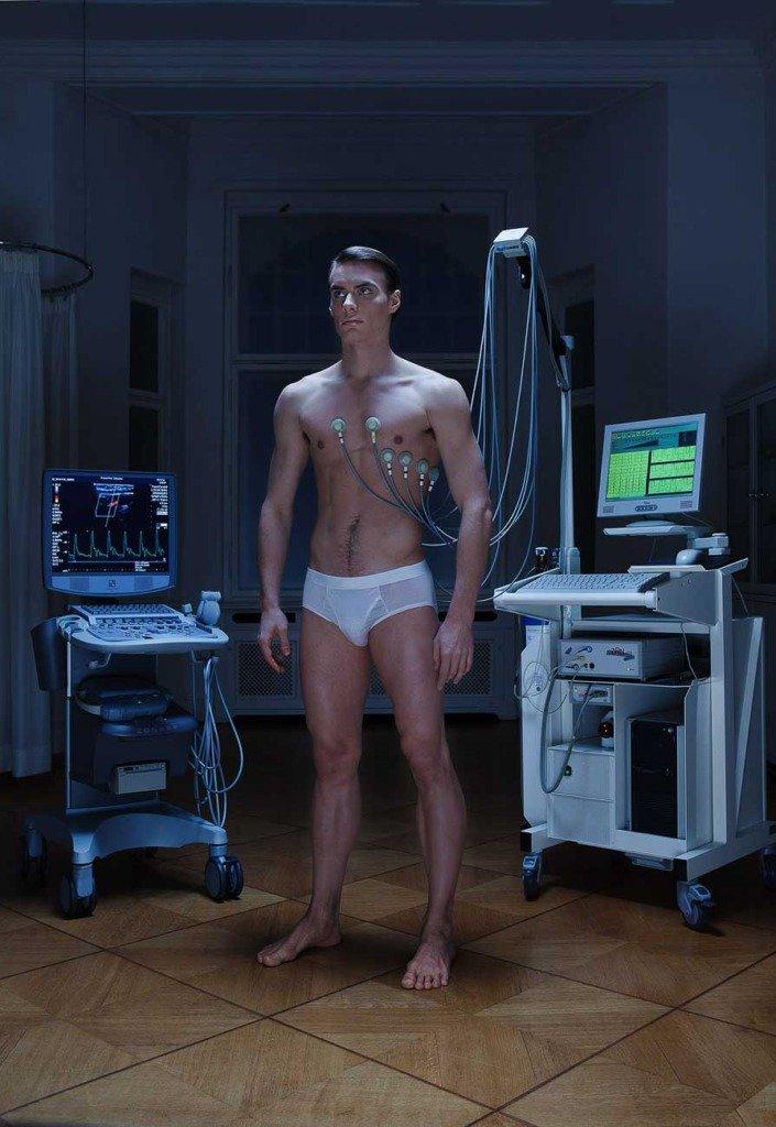 Hochkantfoto von einem Medizincheck eines sportlichen Mannnes in modischer Unterhose in einer Altbaupraxis mit High-Tech-Medizintechnik. Cover für Auditorium Mag