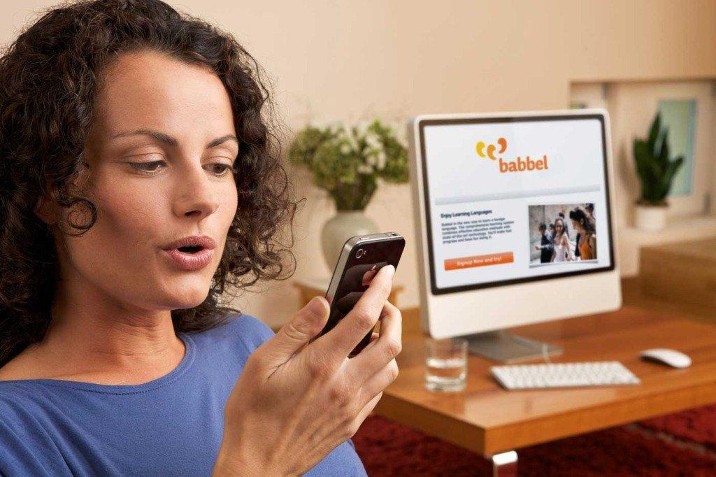 Werbefoto mit einer Frau, die Worte in ein Smarphone artikuliert. Im Hintergrund sieht man die Webseite von Babbel