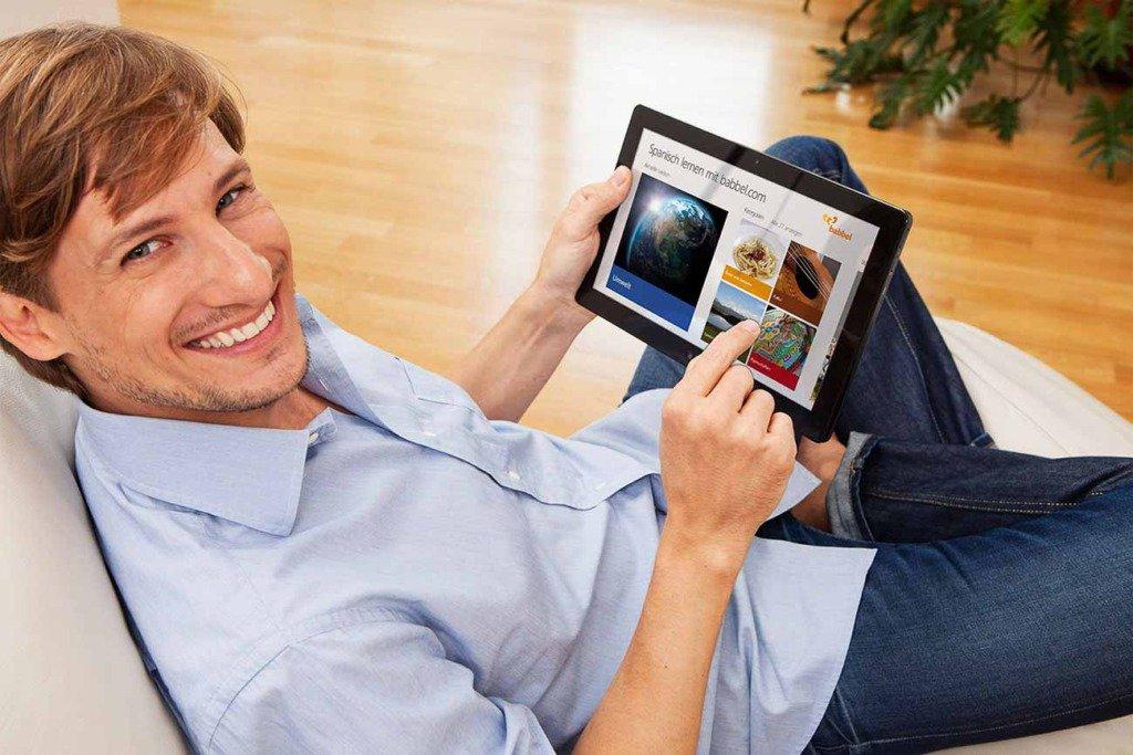 Werbefoto mit einem Mann, der mit einem Tablett-Computer die App von Babbel bedient