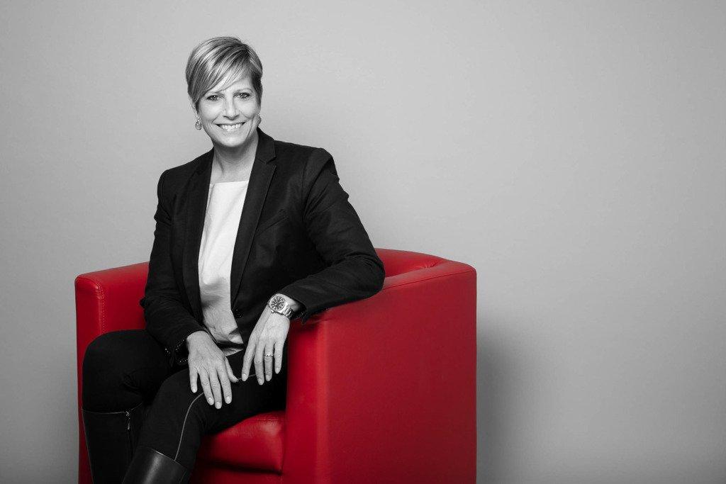 Eine Managerin mittleren Alters sitz im eleganten Business-Outfit auf einem roten Sessel.