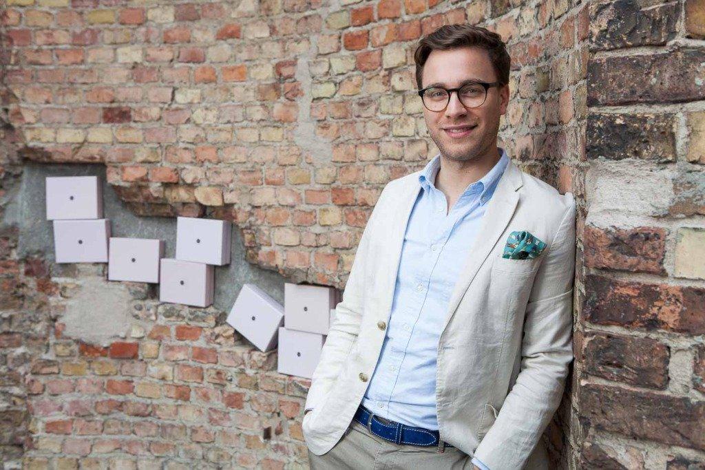 Der CEO des Beauty-Startups Glossybox, Charles von Abercron, steht im Casual Business Look vor Produkten seiner Firma
