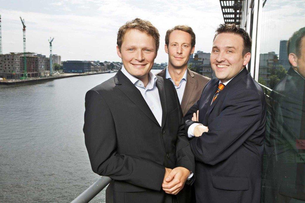 Die drei Vorstände der Berliner Agentur diffferent stehen auf der Terrasse des Unternehmens an der Spree in Berlin