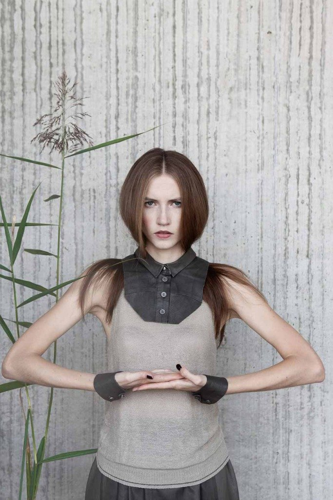 Ein weibliches Model steht mit ökologischer Kleidung vor einer strukturierten Betonwand