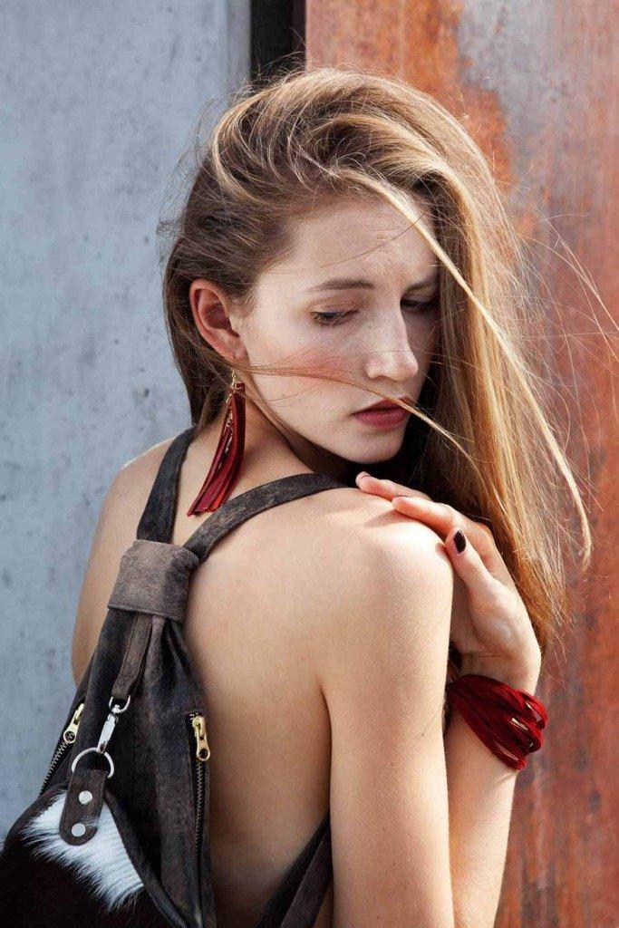 Ein weibliches Model mit ökologischem Rucksack zeigt Schulter und Rücken vor einer Berliner Betonwand
