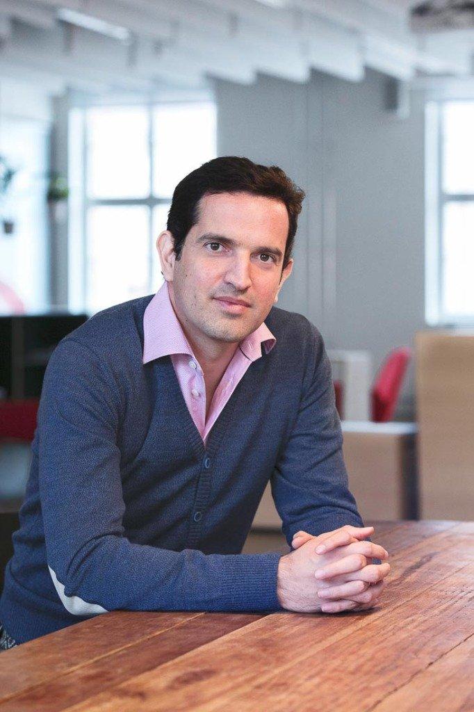 Eduardo Goes, Vorstand von Delivery Hero, sitzt in casual chic gekleidet an einem Holztisch in den Geschäftsräumen von Delivery Hero