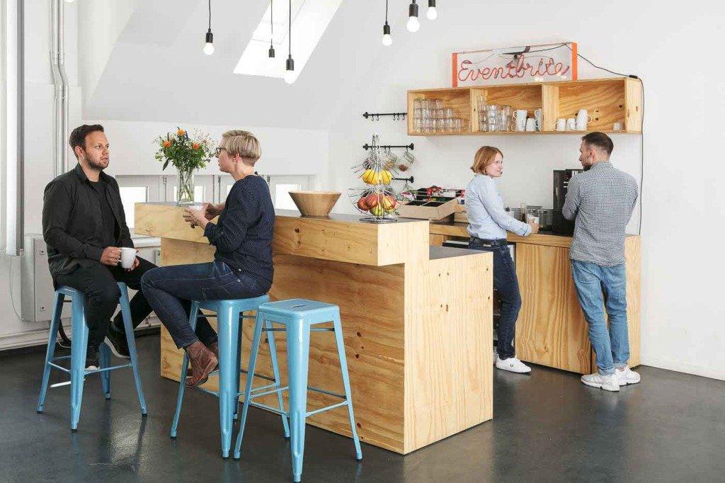Mitarbeiter machen eine Kaffeepause und unterhalten sich in der Büro-Küche