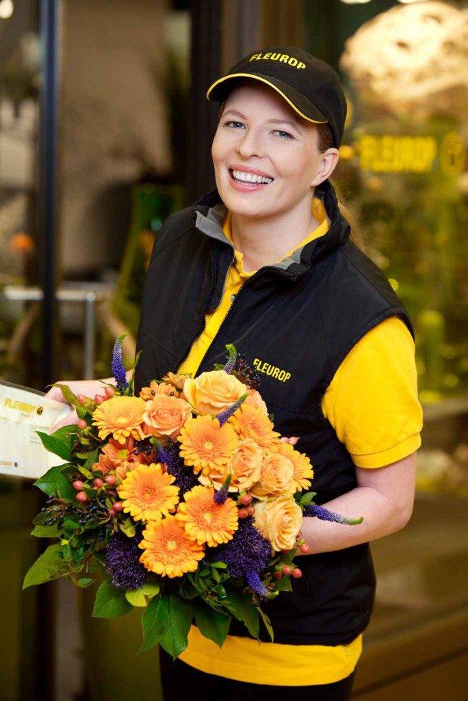 Eine Fleurop-Botin bringt einen Blumenstrauß und lächelt in die Kamera
