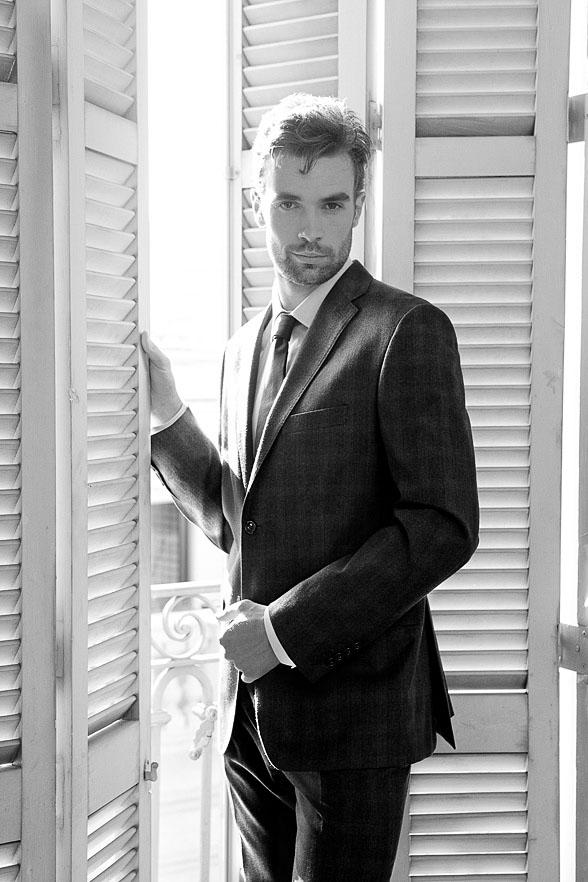 Elegant gekleideter Mann steht an einem Fennsterladen. Schwarz-Weiss Modefotografie.