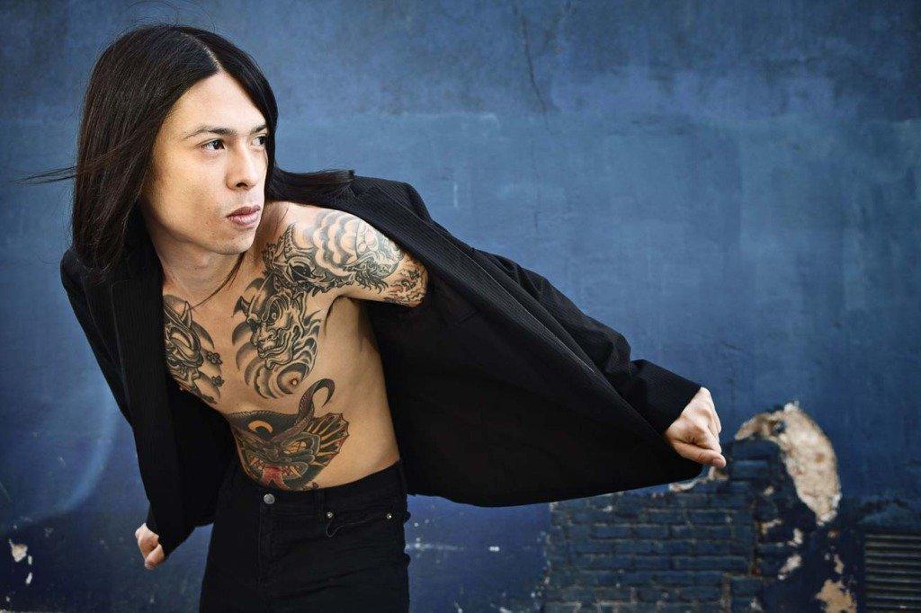 chinesisch-lateinamerikanisches männliches Model steht mit nackter Brust und offenem Jackett vor einer blauen Wand. Modefoto für Grisby Menswear