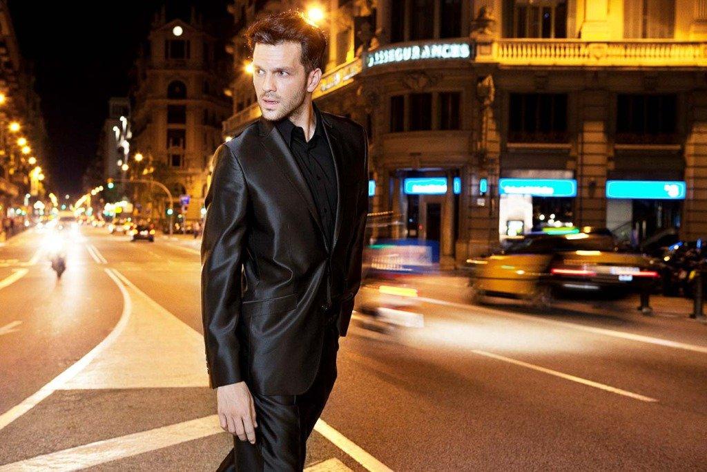 männliches Model im eleganten schwarzen Anzug überquert eine große Straße bei Nacht. Modefoto aus Barcelona.