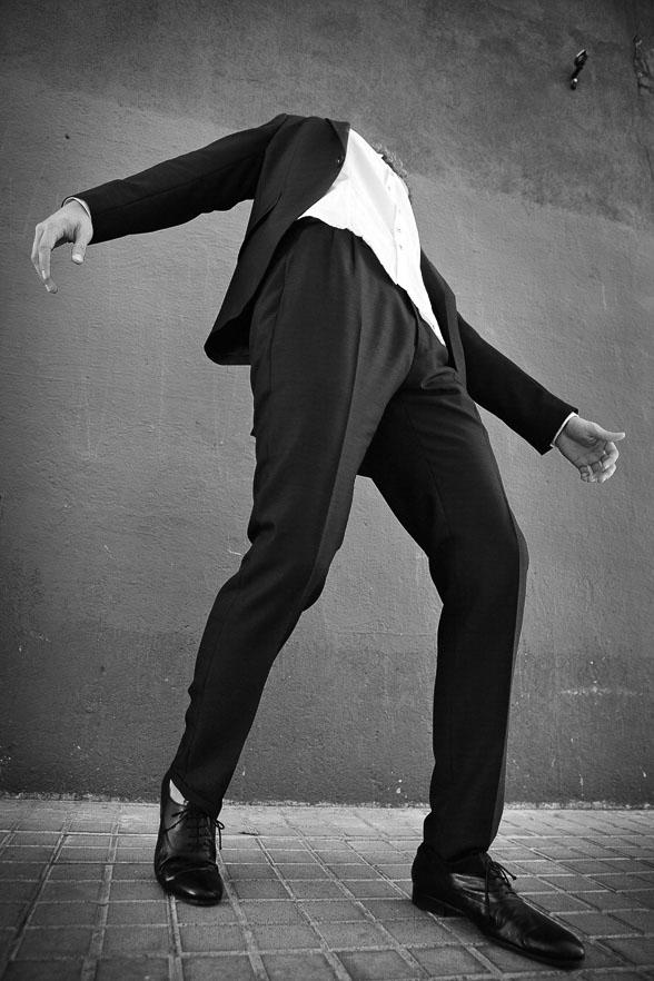 männliches Model steht im Anzug und fällt nach hinten. Modefoto für Grisby Menswear