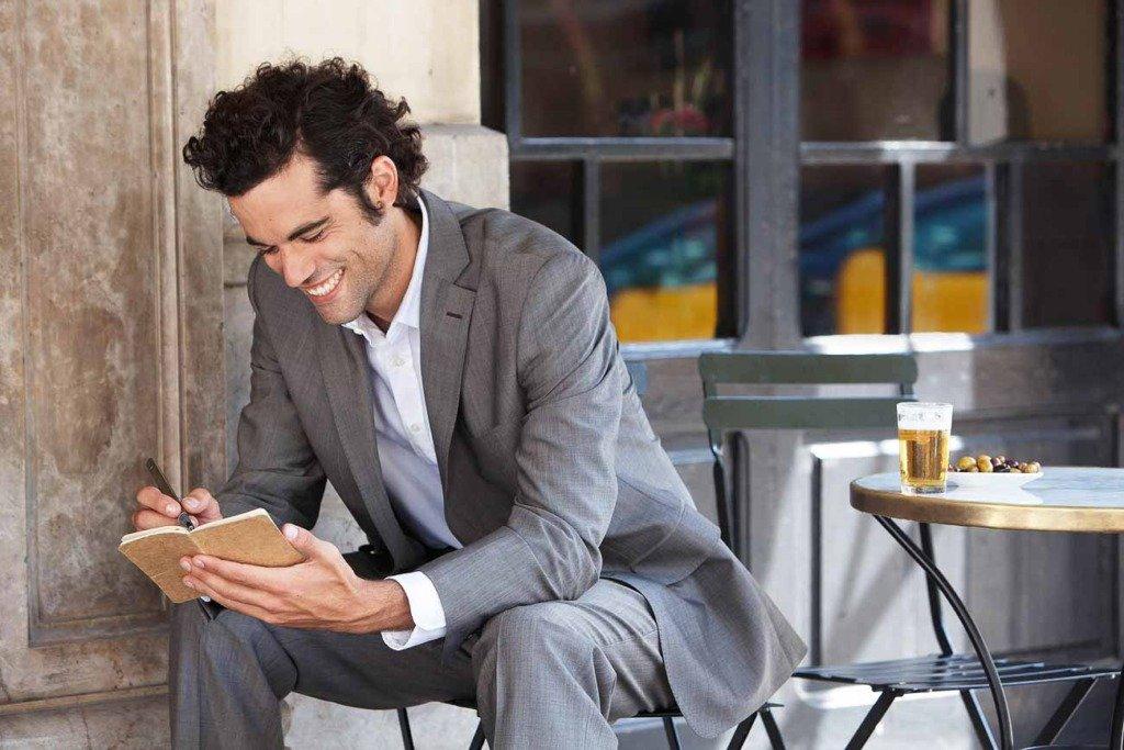 spanischer Mann im Sommeranzug sitzt in Barcelona auf einer Terrasse und notiert sich etwas