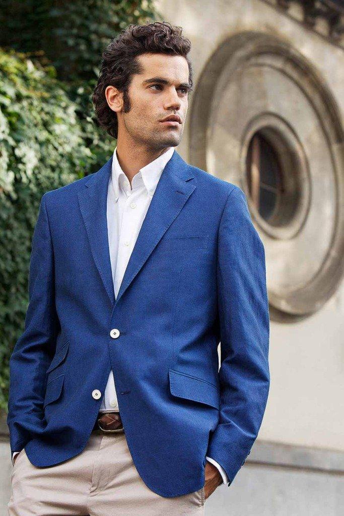 männliches Model in eleganter Kleidung steht vor mediterraner Wand. Modefoto für Grisby Menswear