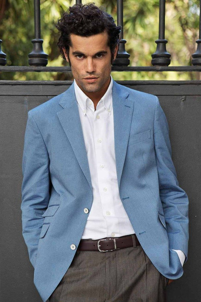 spanisches männliches Model steht im blauen Jackett an einer metallenen Parktür und guckt in die Kamera