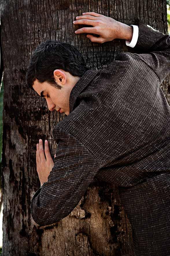 Ein männliches Model lehnt mit geschlossenen Augen an einem großen Baumstamm