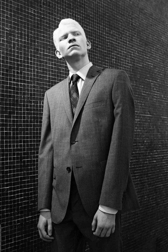 ein männliches Albino-Modell im Herrenanzug steht vor einer Wand aus kleinen Kacheln. Schwarz-Weiss-Modefoto mit Beauty-Spot
