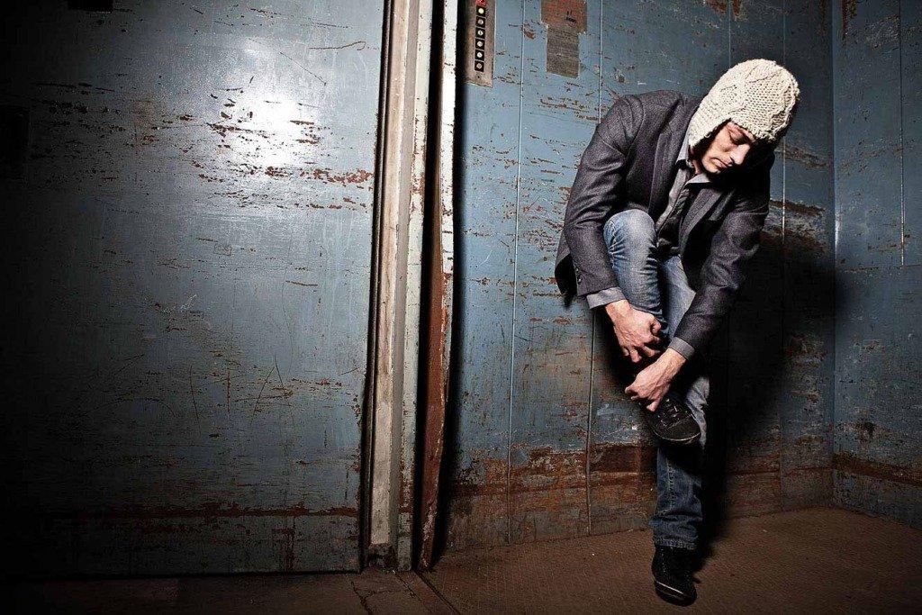junger Mann mit Jackett und Wollmütze steht in einem Industrieaufzug auf einem Bein und richtet sich seinen Schuh