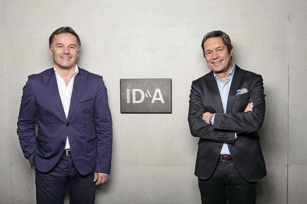 Die Geschäftsführer des Berliner Immobilienentwicklers ID&A, Frank Hemprich und Ulrich Trautmann, stehen in eleganten Jacketts vor einer Waschbe
