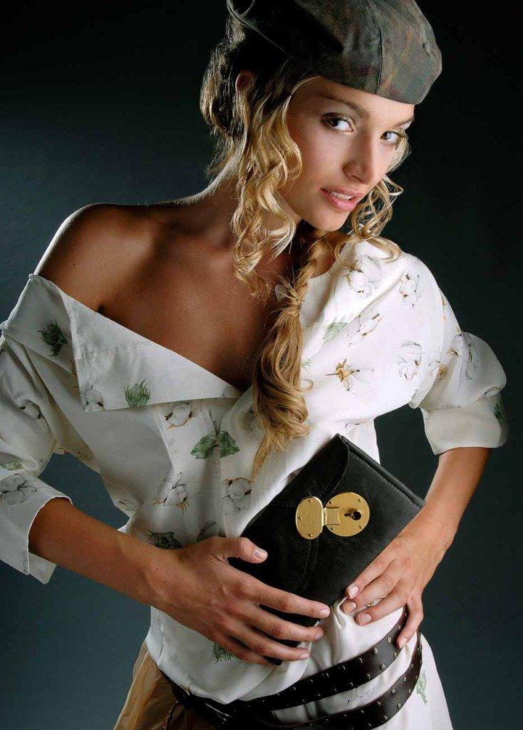 junge Frau mit Hut und Damentasche schaut in die Kamera