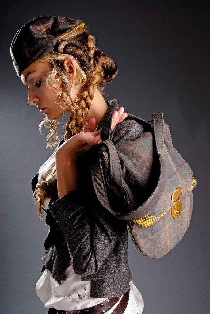 blonde junge Frau mit Hut und Damentasche über der Schulter schaut nach unten