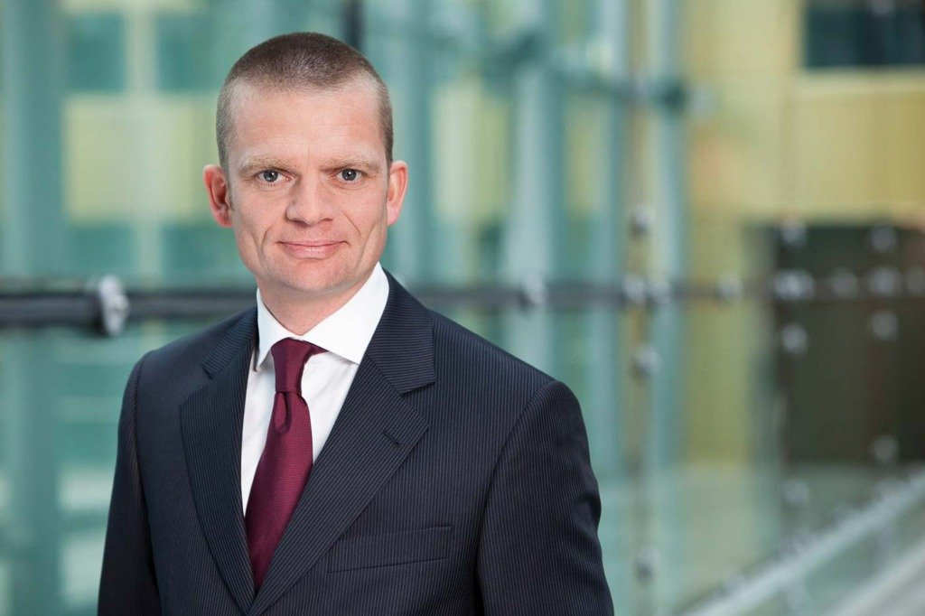 Jan Beyer, Vorstand von Axel Springer SE wurde vor einer Glaswand und der goldenen Fassade des Axel Springer Hochhauses in formellem Outfit porträtiert