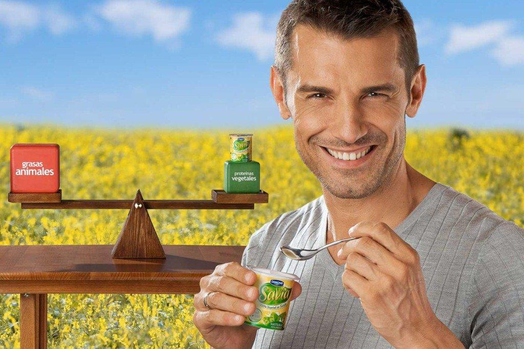 Der spanische TV-Moderator jesus vazquez isst einen Joghurt. Er wirbt als Testimonial von Danone für Savia-Joghurt. Im Hintergrund ist eine Blütenwiese