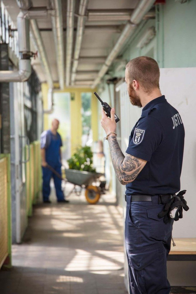 Wärter in Uniform überwacht die Arbeit der Insassen einer Gefängnisgärtnerei. Fotoreportage über die Arbeit der Justizvollzugsbeamten in Berlin Plötzensee