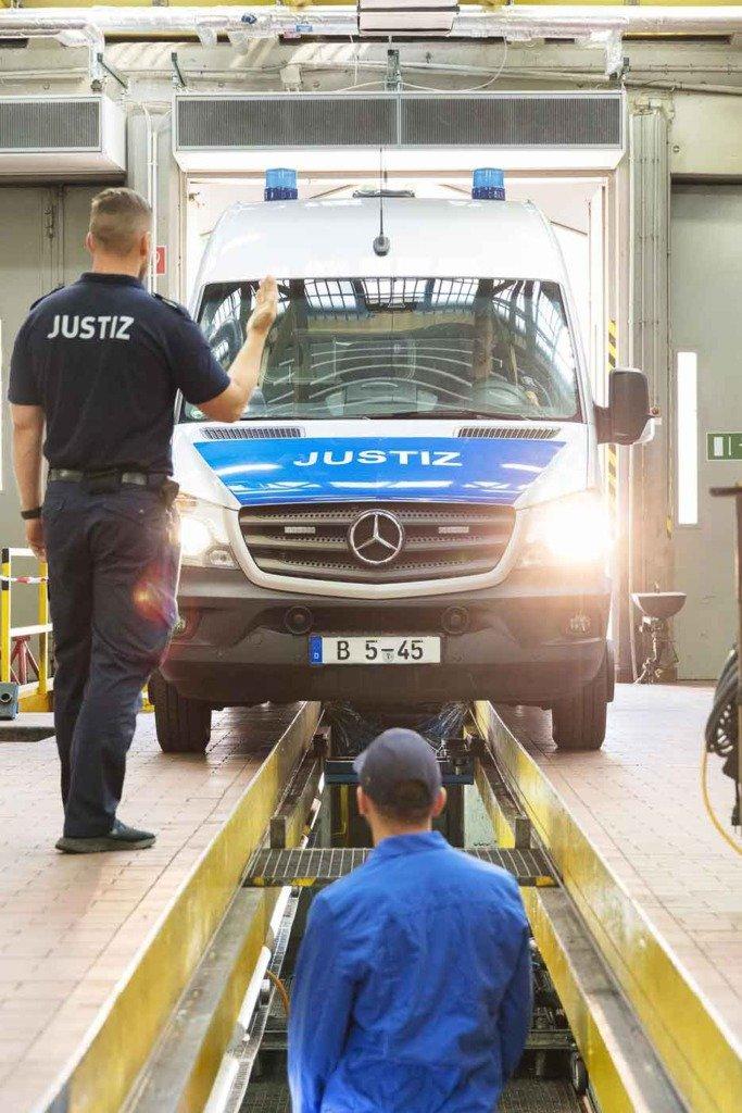 Wärter in Uniform lotst ein Justiz-KFZ über einen Werkstattgraben. Fotoreportage über die Arbeit der Justizvollzugsbeamten in Berlin Plötzensee