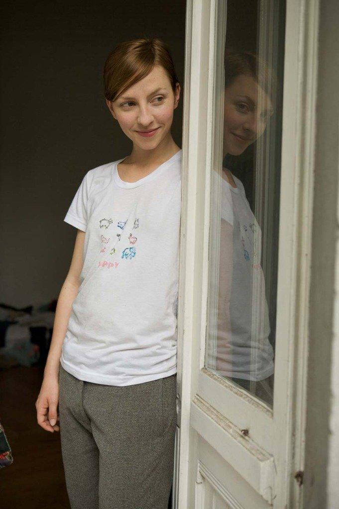 Schauspielerin Katharina Schüttler steht an einer Balkontür und präsentiert ihr Lieblings-T-Shirt