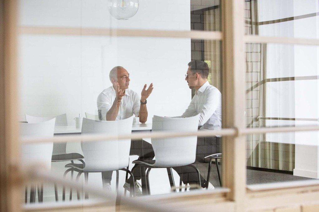 KENFO Manager sitzt mit Mitarbeiter in einem One-To-One-Meeting im Berliner Hauptquartier