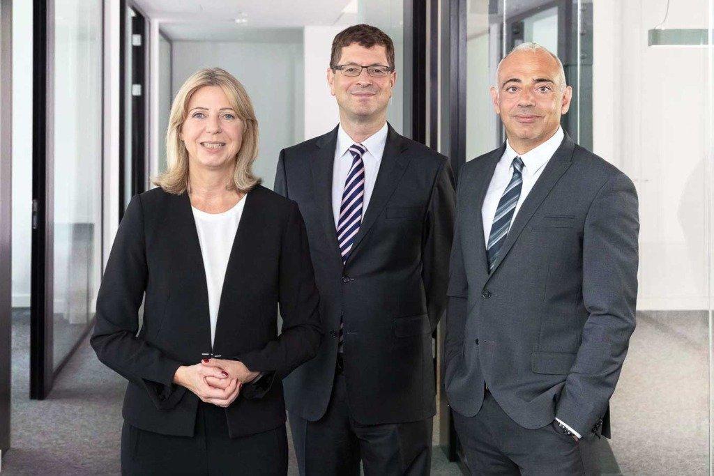 Die drei Vorstände des deutschen Staatsfonds KENFO stehen in den Geschäftsräumen der Firma in Berlin