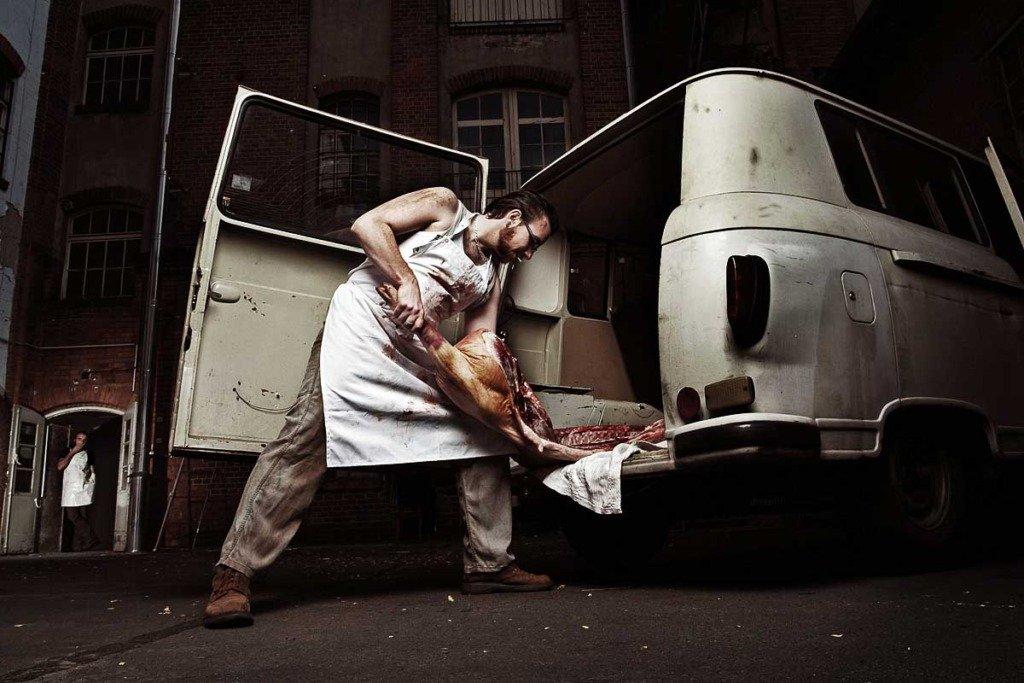 Der deutsche Musikproduzent Kraans de Lutin trägt eine Schweinehälfte durch einen historischen Berliner Hinterhof