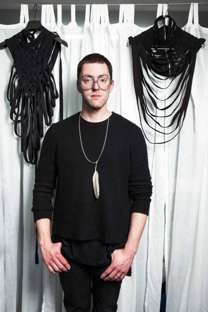 Für das Modemagazin Women's Wear Daily posiert der dänische Modedesigner Mads Dinesen ganz in schwarz vor Kollektionsstücken in seinem Berliner Atelier