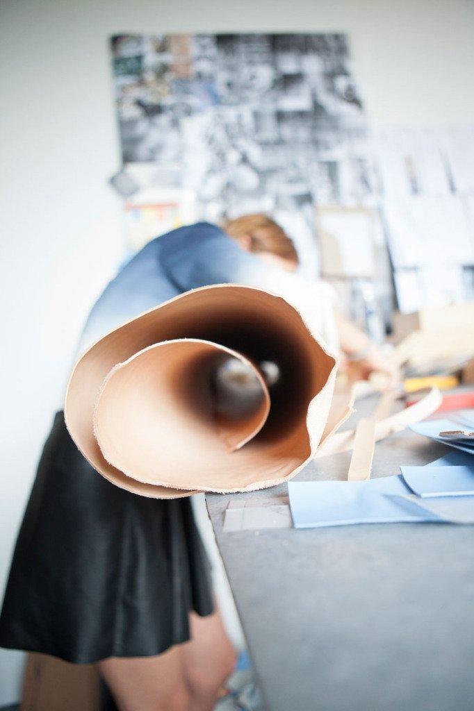 Marina Hoermanseder beugt sich über Rohleder-Rolle für die Produktion ihrer Showroomkollektion. Fetisch-Mode-Atelier in Berlin. Fotodokumentation für WWD