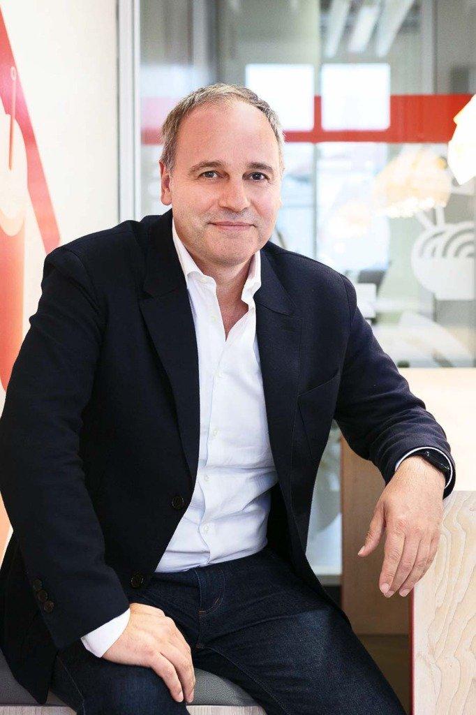 Martin Enderle sitzt im Anzug bei Delivery Hero in Berlin in einer modernen Lounge auf einer Bank