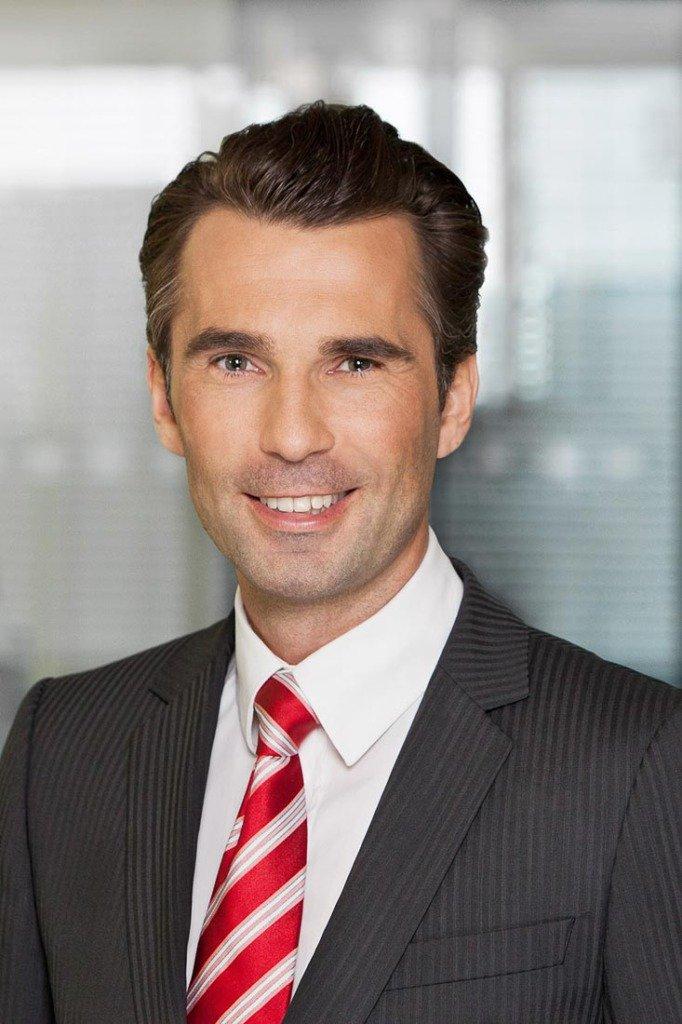 Ein glücklicher Manager der Firma Media Impact steht in Anzug und Krawatte vor einem Business-Hintergrund