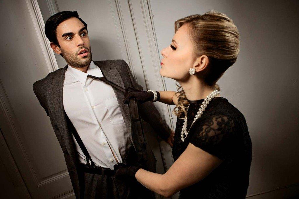 Frau attakiert elegant gekleideten Mann in einer Wohnung. Vintage-Modefoto im Park Ciutadella Barcelona