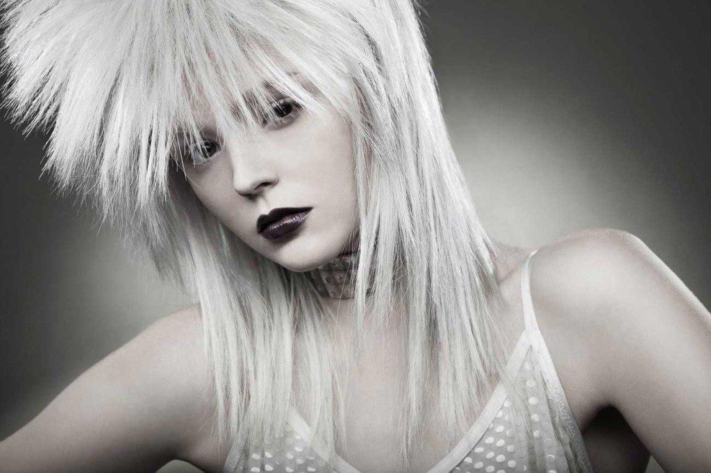 Portrait eines Fashionmodels mit weisser 80er Jahre Rocker-Perrücke und Punk-Halsband im Fotostudio