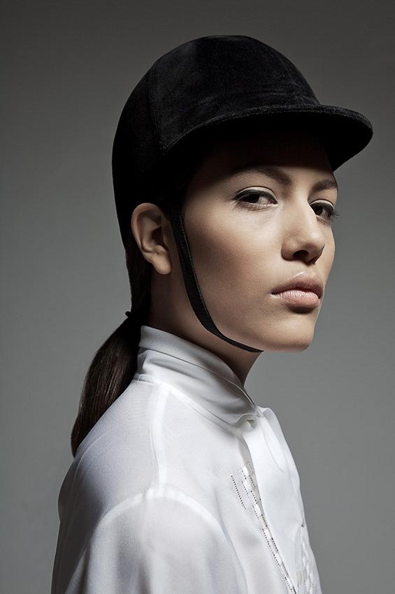Modefoto einer Frau mit Reiterhut und weißer Bluse im Portrait