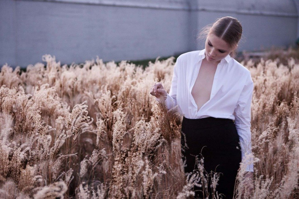 Ein weilbliches Model steht mit halbgeöffneter weißer Bluse in einem Kornfeld -