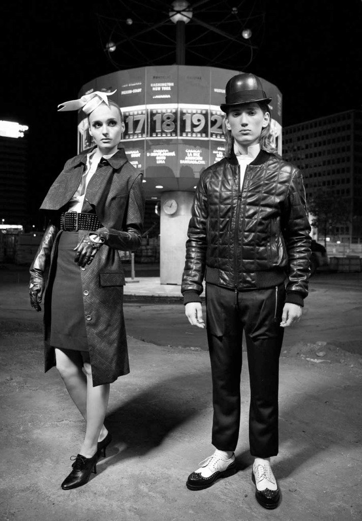Schwarz-Weiss-Modefoto von Frau und Mann vor der Berliner Weltzeituhr. Nächtliches Schwarz-Weiss-Modefoto